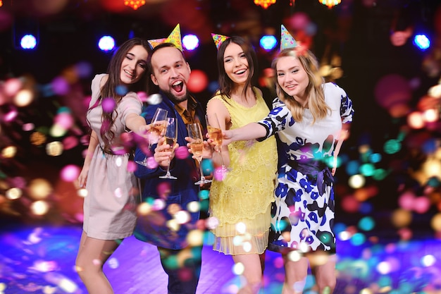 Company of cheerful friends in festive hats to celebrate the event Premium Photo