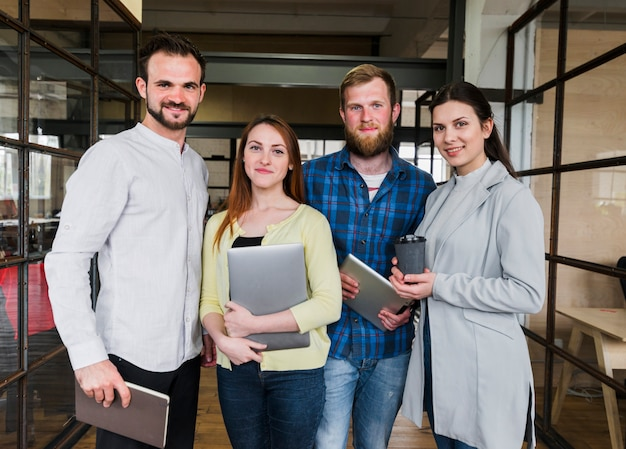 Company colleagues stand with confident expression Free Photo