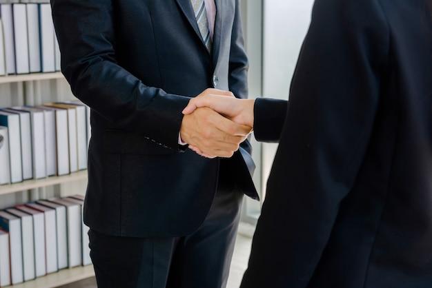 Сотрудники компании пожимают друг другу руки Premium Фотографии
