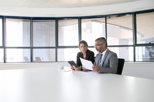 Руководители компаний анализируют и обсуждают отчеты. два коллег по бизнесу сидели вместе, смотрели на документ, держали планшет и разговаривали. широкий план. концепция коммуникации Бесплатные Фотографии