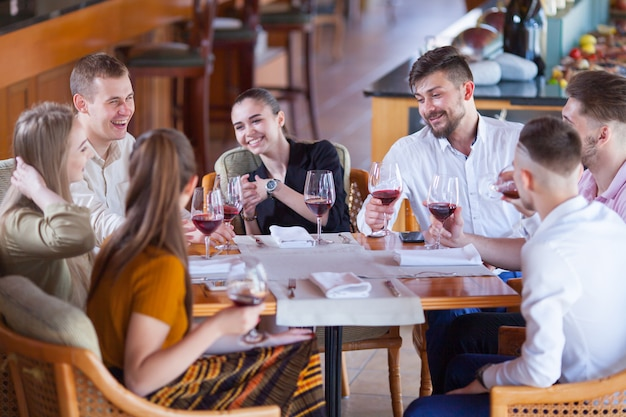 Company of friends celebrates meeting in a restaurant. Premium Photo