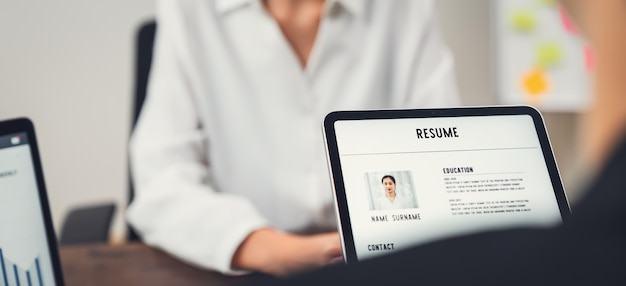 Company human resource (hr) is holding a resume application on tablet in hand. young asian woman talking to give job interviews. Premium Photo