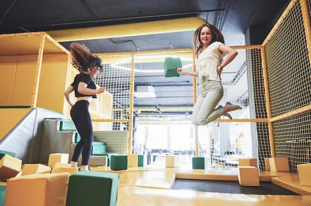 La compagnia è una giovane donna che si diverte con i blocchi morbidi nel parco giochi per bambini in un centro di tappeti elastici. Foto Gratuite