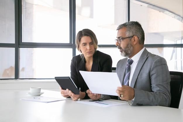 Leader dell'azienda che analizzano i rapporti. due colleghi di lavoro seduti insieme, guardando il documento, tenendo tablet e parlando. colpo medio. concetto di comunicazione Foto Gratuite