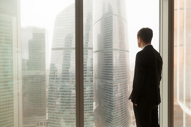 Company official looking through window in office Free Photo