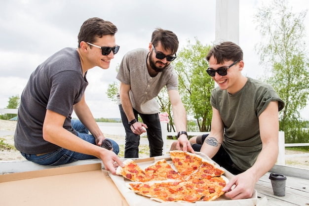 Company of smiling friends eating pizza on picnic Free Photo