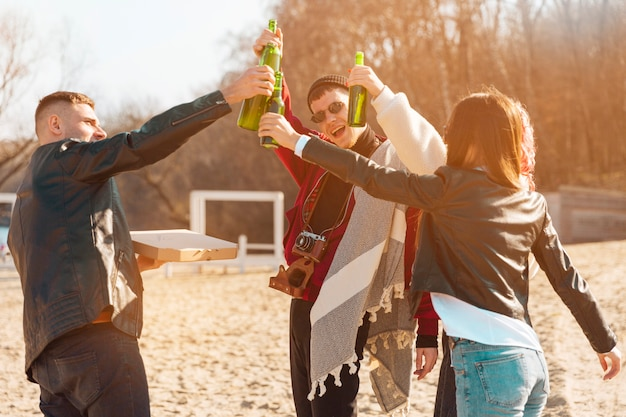 Company of smiling friends having fun with beer in open air Free Photo