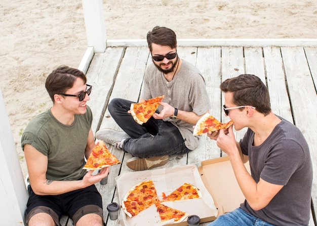 Company of young guys eating pizza on beach Free Photo