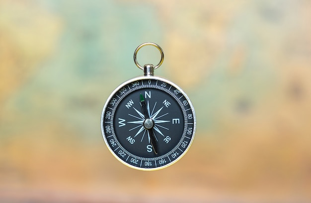 Compass on a blurred background of an old map Premium Photo