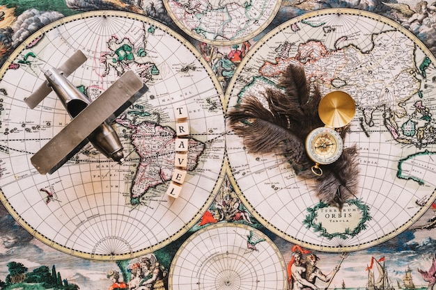 Compass and feathers near travel writing and plane Free Photo