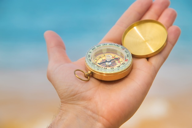 Compass on hand in the sea and the beach. Premium Photo