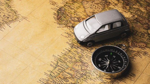 Compass and miniature car toy on a antique map. - travel and adventure concept. Premium Photo