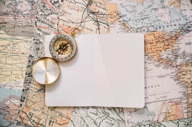 Compass and paper on map Free Photo