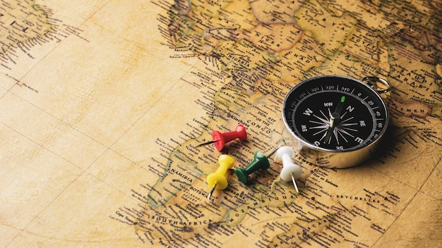 Compass and pushpin pile on a antique map. - travel and adventure concept. Premium Photo