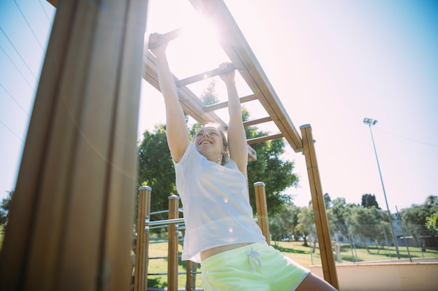 Competitive young woman exercising on monkey bars Free Photo