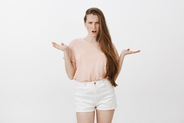 Adolescente frustrato lamentarsi che posa contro il muro bianco Foto Gratuite