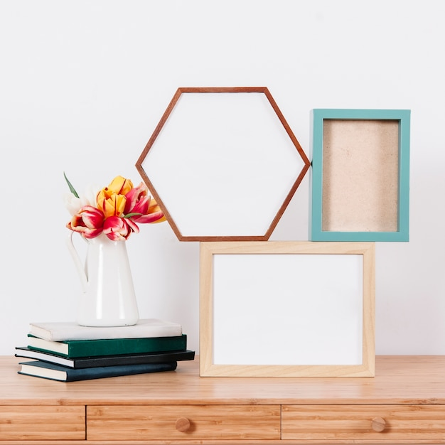 Composed photo frames and flowers on table Free Photo