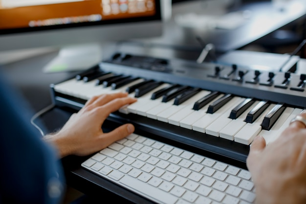 Composer hands on piano keys in recording studio. music production technology, man is working on pianino and computer keyboard on desk. close up concept. Premium Photo