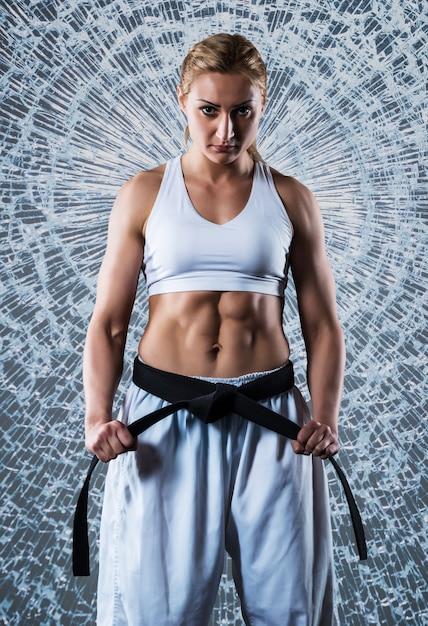 Composite image of karate girl wearing white sportswear and black belt, breaking glass in jump Premium Photo