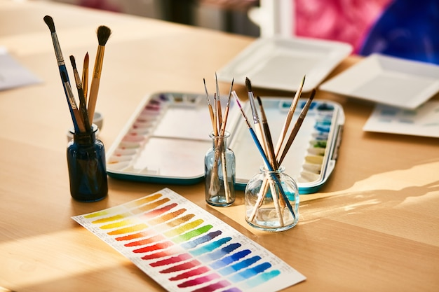 Composition on the artist's workplace, glasses with paint brushes and swatches Free Photo