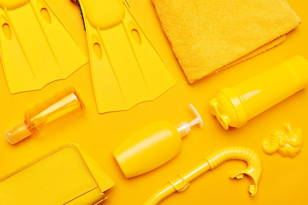 Composition of beachwear and accessories on a yellow Premium Photo