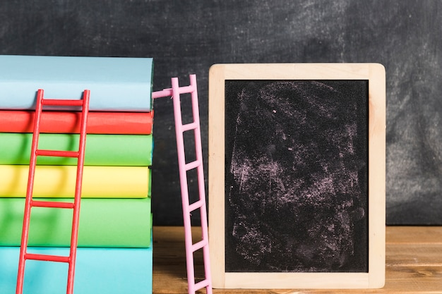 Composition of books with ladder near chalkboard Free Photo