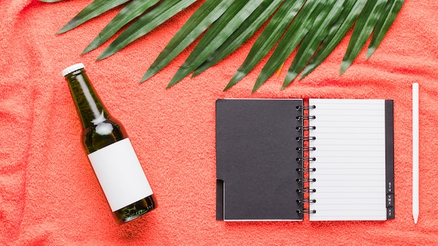 Composition of bottle notebook pen and green leaf Free Photo