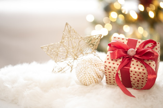 Composition of a christmas gift and new year's decoration on a light background with gerland lights. Free Photo