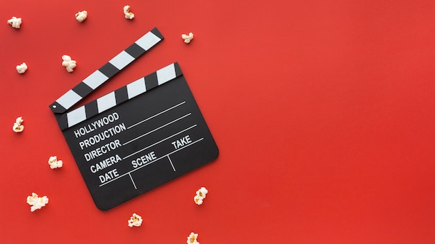 Composition of cinema elements on red background with copy space Free Photo
