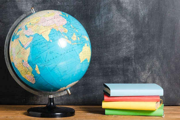 Composition of colorful books and globe Free Photo