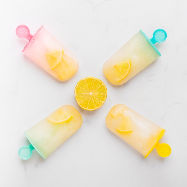 Composition of cut lemon and ice popsicle with citrus on colorful sticks Free Photo
