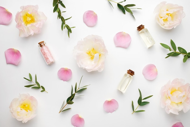 The composition of flowers, rose petals, eucalyptus branches and essential oil Premium Photo
