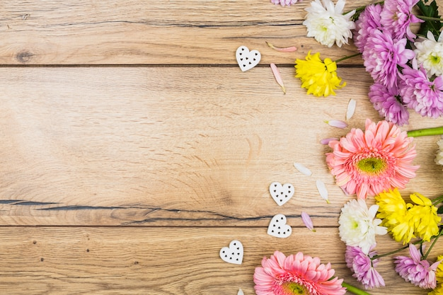 Composition of fresh flowers near ornamental hearts Free Photo
