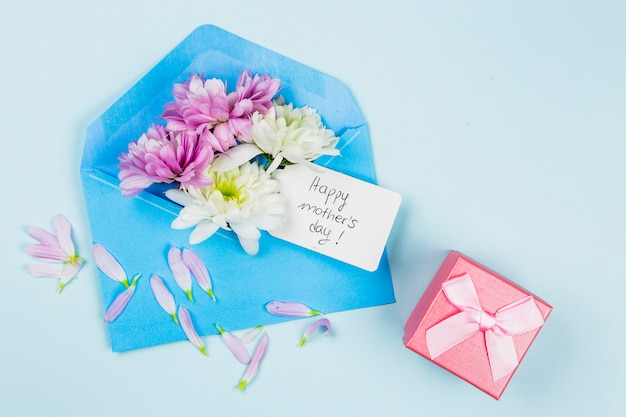 Composition of fresh flowers with tag in envelope near present Free Photo