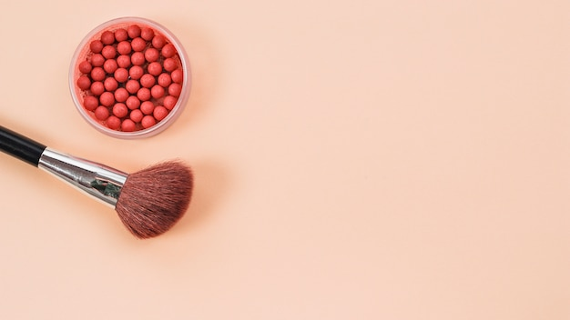Composition from makeup brush and rouge on light background Free Photo