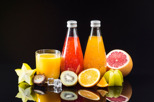 Composition of fruit and juices on black background Free Photo