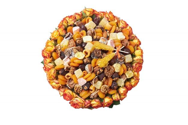 白い背景の上のナッツとオレンジと黄色のドライフルーツの花束の形で組成 Premium写真