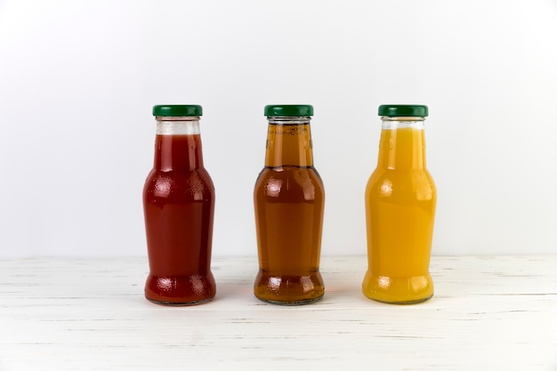 Composition of juice bottles on table Free Photo