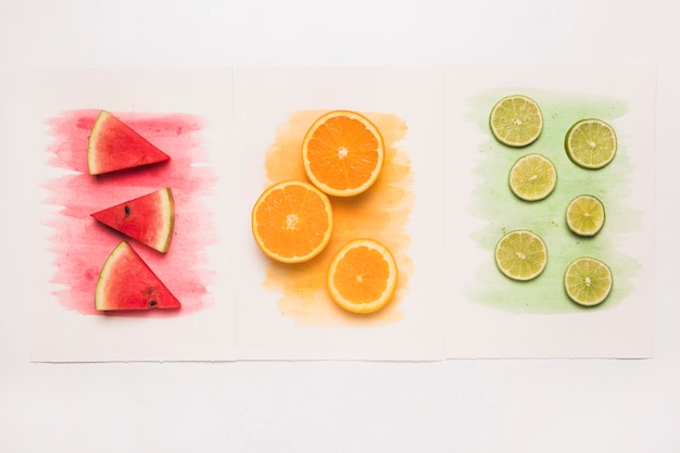 Composition of juicy cut fruits on colored watercolor splash Free Photo
