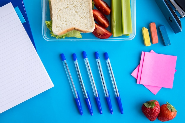 Composition of lunchbox and stationery on table Free Photo