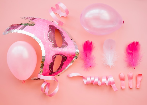 Composition of mask near balloons and feathers Free Photo