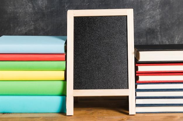 黒板と色とりどりの本の構成 無料写真