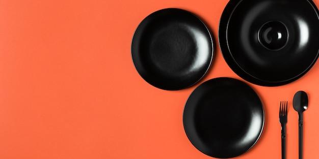 コピースペースとオレンジ色の背景に異なるサイズのプレートの構成 無料写真