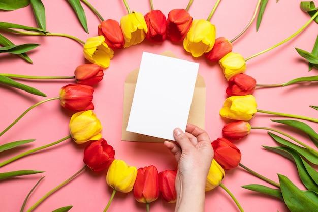 新鮮な花、赤いチューリップの花束、封筒と紙テクスチャ背景の構成。国際女性の日、母の日挨拶コンセプト。 Premium写真