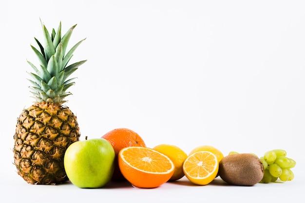 Композиция из смешанных свежих тропических фруктов на белом фоне Premium Фотографии