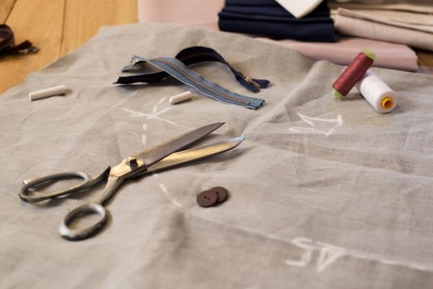 他の縫製仕立て道具による針と糸の構成。糸、はさみ、ボタン、ミシン用品のスプール。はさみ、ボタン、糸、指ぬきの生地のクローズアップ。 Premium写真