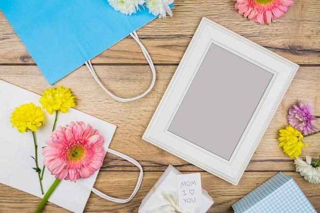 生花、プレゼントボックス、紙包みの近くのフォトフレームの構成 無料写真
