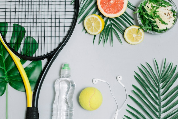 Composition of tennis racket and healthy food Free Photo