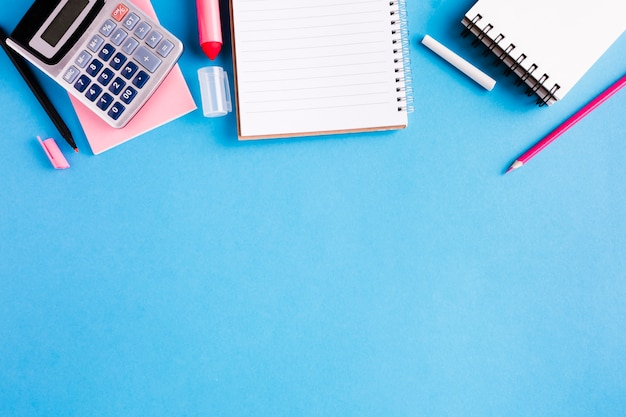 Composition of office supplies on blue surface Free Photo