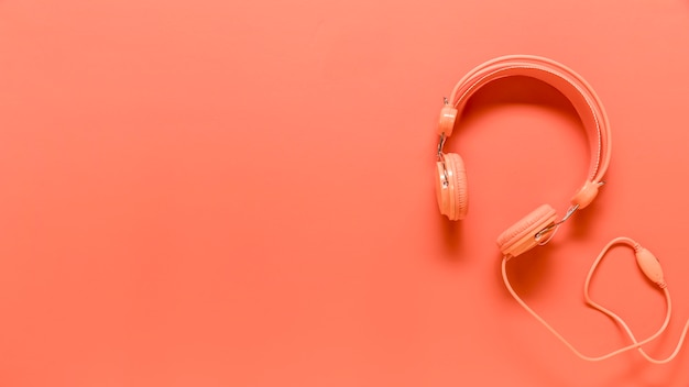 Composition of pink headphones with usb wire Free Photo